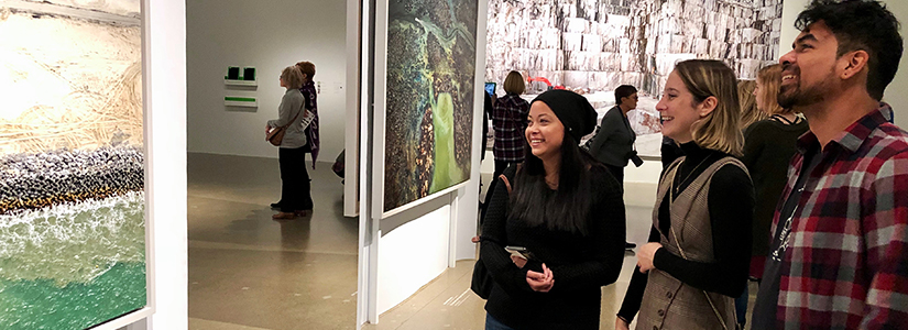 photo of three students looking at a painting hanging on a wall